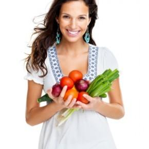 Vegetarian woman with hands full of vegetables